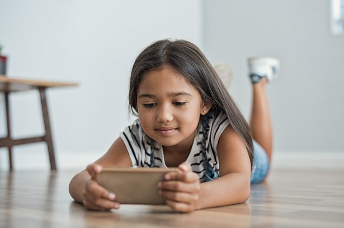 A young girl looks at the screen of a mobile phone.