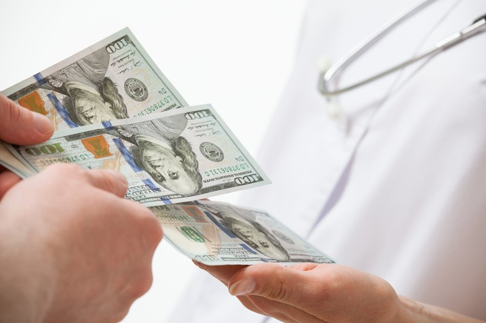 Person handing three $100 bills to a person wearing a stethoscope.