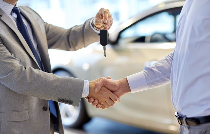 A salesman hands car keys to a customer while shaking his hand.