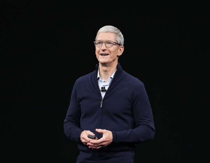 Cook is standing before a black backdrop on stage at an Apple event.