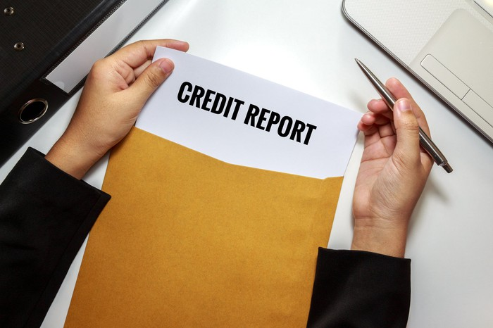 A person opening an envelope with a credit report inside.