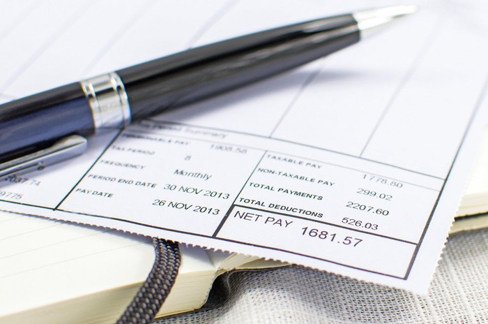 A pay stub with an ink pen on top of it.