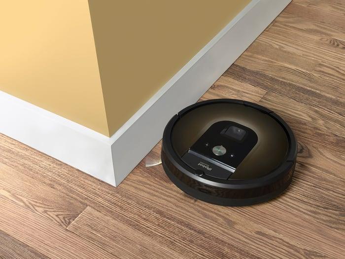 iRobot's Roomba 980 robotic vacuum rounding a corner on a hardwood floor