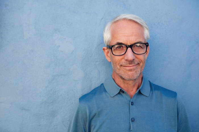 Senior male in glasses against a blue background.