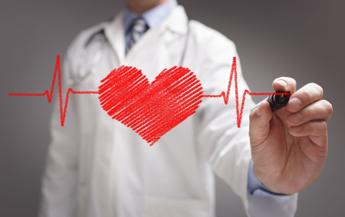 A person in a white lab coat uses a red marker to draw a heart between two beats on a transparent surface.