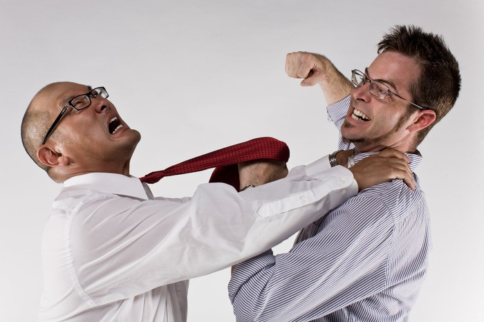 Two men attack each other.
