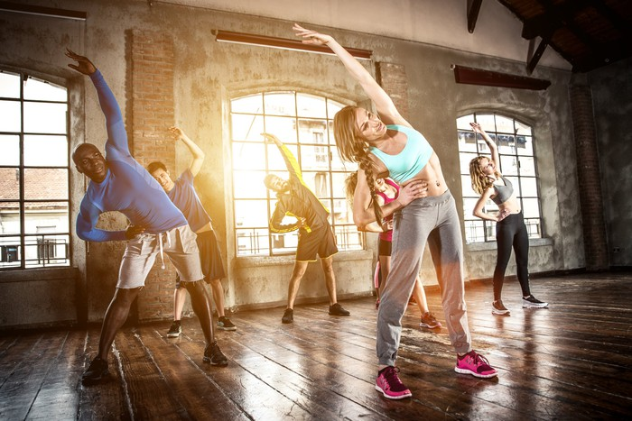 Six younger men and women dressed in workout clothing stretching to their right sides while taking an exercise class in a room with big windows.