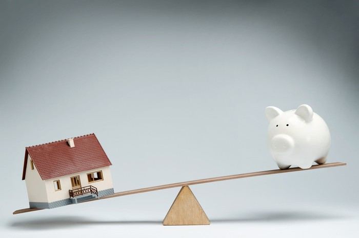 Model home and piggy bank balancing on a fulcrum.