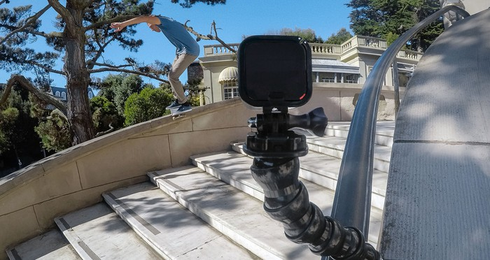 A GoPro camera recording a skateboarder doing tricks down an outdoor flight of stairs.