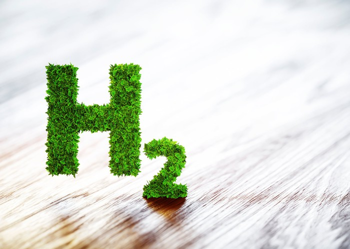 A green hydrogen symbol floats on a wooden table.