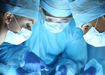 Three surgeons in blue over an operating table