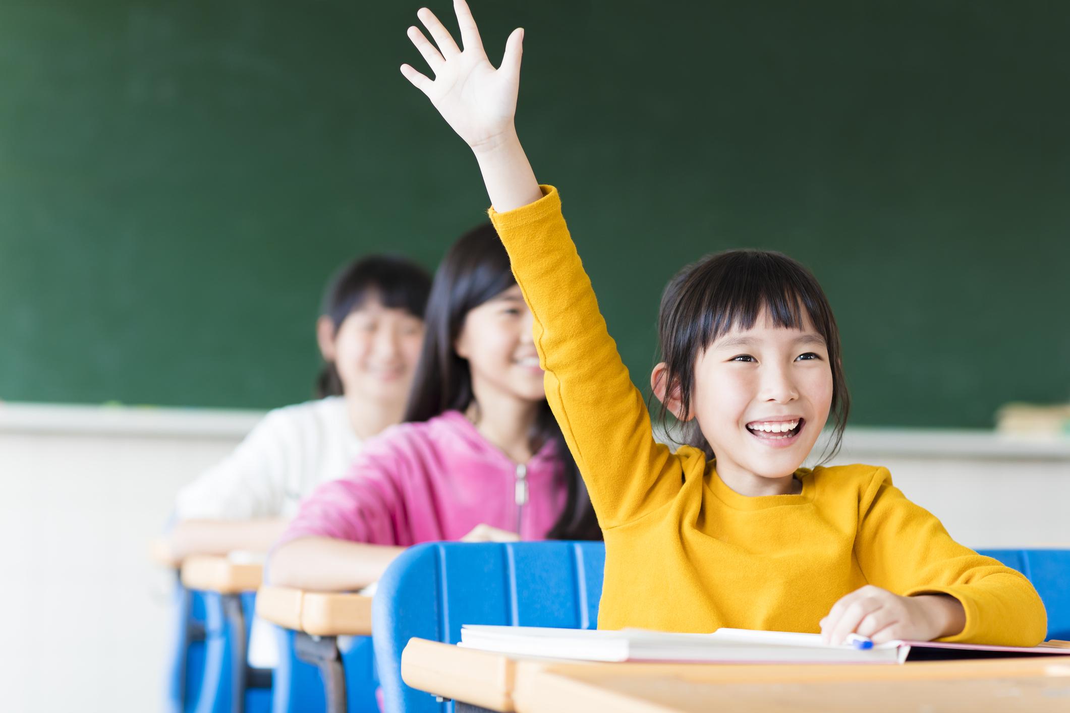 An Asian girl raising her hand in a classroom