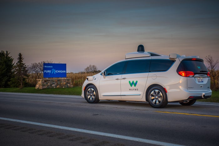 A White Chrysler Minivan With Waymo Markings And Visible Self Driving Sensor Hardware Is Shown