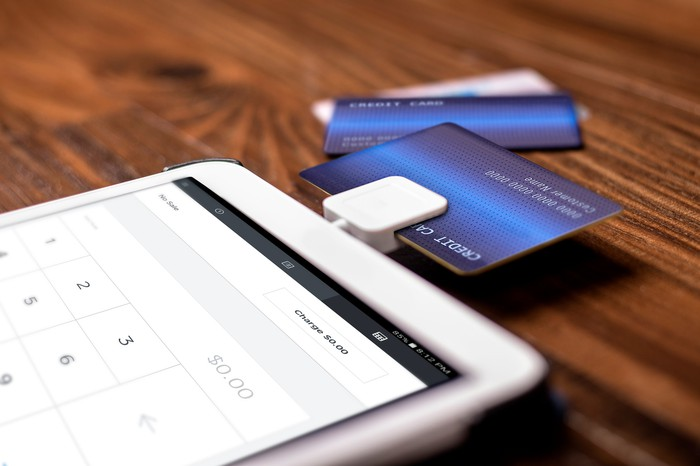 A credit card reader attached to a mobile device, with several credit cards