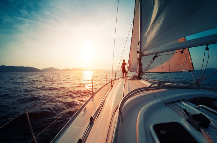Yacht on open water sailing into the sunset.
