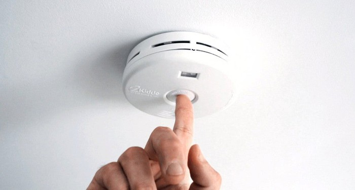 A person pushing the test button on a smoke alarm.