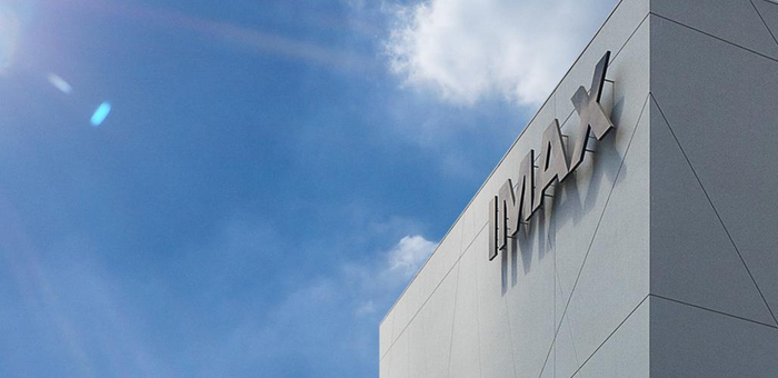 IMAX logo in the form of a sign at the corner of a tall building, set against blue skies.