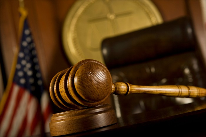 A closeup of a gavel in front of a judge's chair in a courtroom