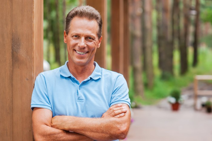 A smiling man outdoors in a blue polo shirt
