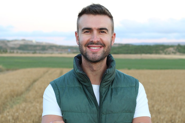 A smiling man outdoors wearing a green vest