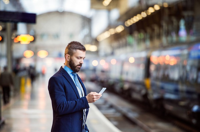 A man in a suit and tie looking at his smartphone while waiting for the subway.