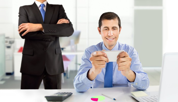 A professionally dressed male checks his phone while a man in a suit and tie stands behind him with arms crossed