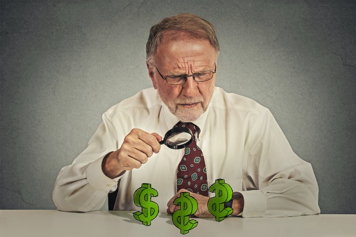 A senior man with a magnifying glass looking at dollar signs on a table.