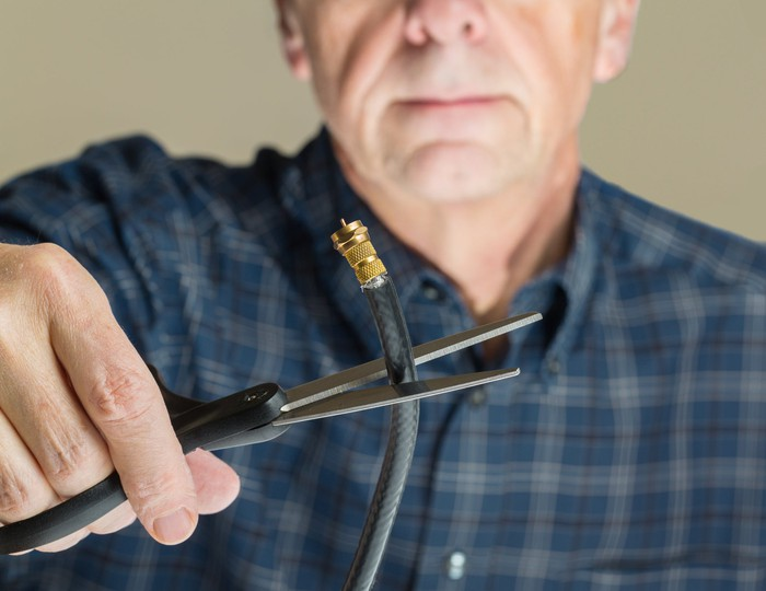 A man holds a cable cord with a pair of scissors.