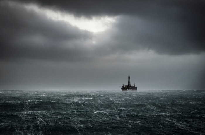 An offshore drilling rig in stormy weather.
