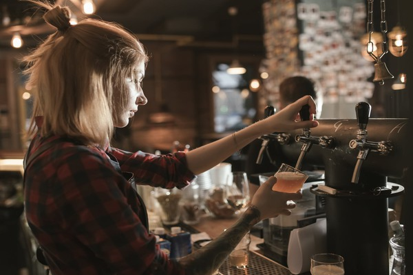 female bartender bar tap craft beer getty