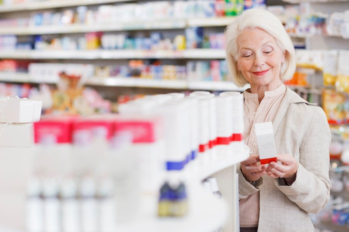 A senior woman holds an item she picked up off a shelf in a pharmacy store.