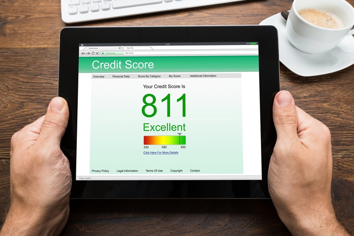 A pair of hands hold a tablet showing a credit score of 811. Behind the tablet on the same tabletop are a computer keyboard and a cup with a drink in it.