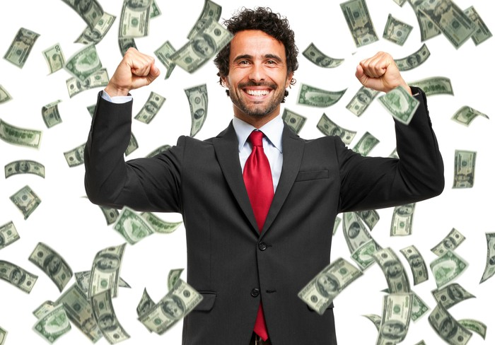 A businessman smiles with his arms raised as $100 bills fall from the sky around him.