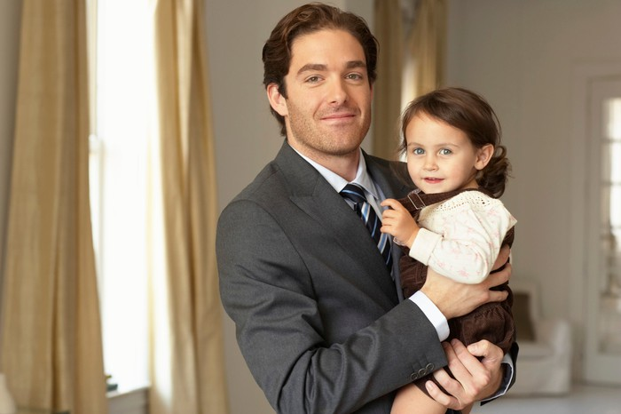 Professionally dressed man holding baby girl