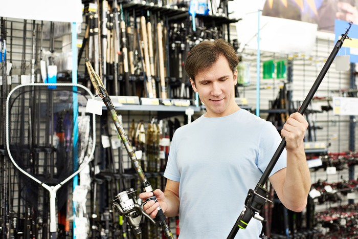 A man holds up two fishing rods inside of a store.