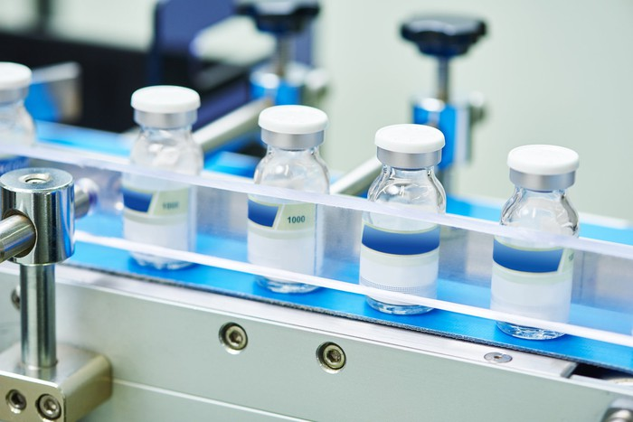 Several bottles of drug products on a manufacturing line.