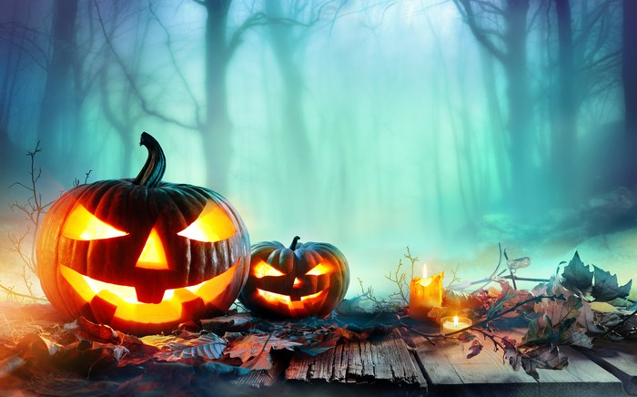 two Jack o lanterns sitting in misty forest at night