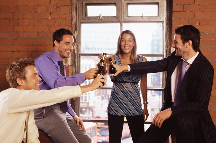 Four pofessionals toasting with beer bottles in hand