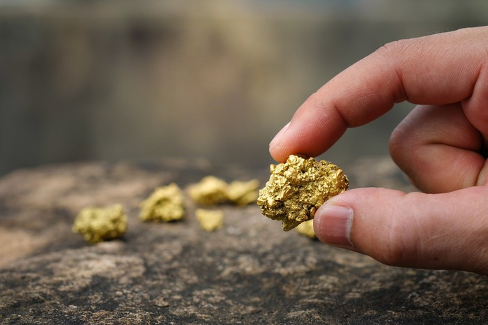 A man holds a piece of gold ore between his thumb and forefinger.