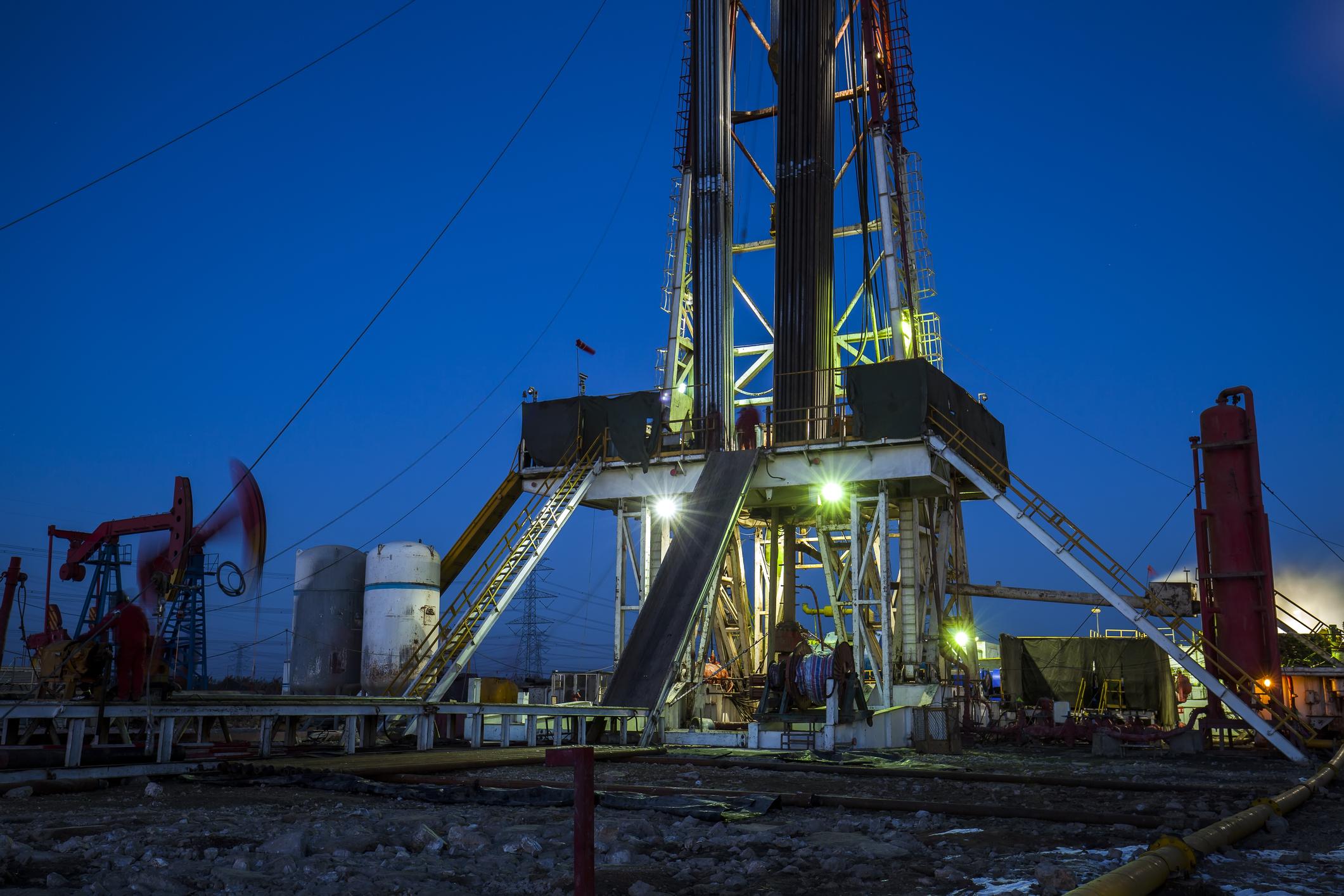 An oil drilling rig near some oil pump jacks.