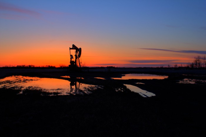 An oil pump with the sun setting in the background after the rain.