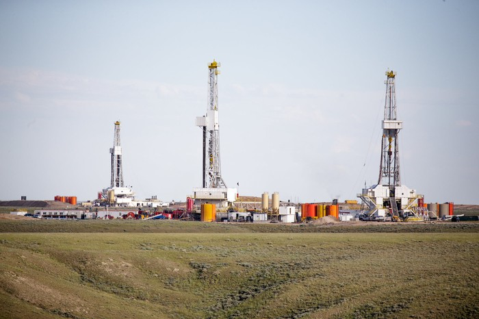 Multiple land drilling rigs in a field.