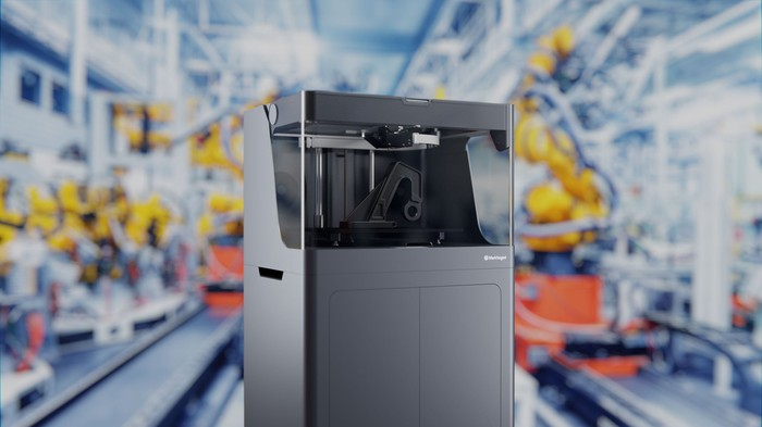A Markforged X5 composite 3D printer with an out-of-focus view of a factory in the background.