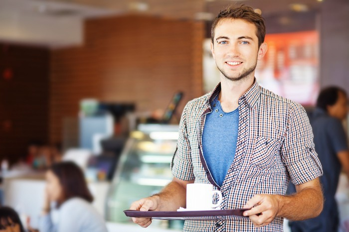 Young man at a fast casual restaurant, holding a mug on a tray.