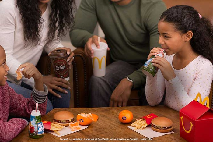 Children gathered around a table with parents eat a McDonald's kids meal offering.