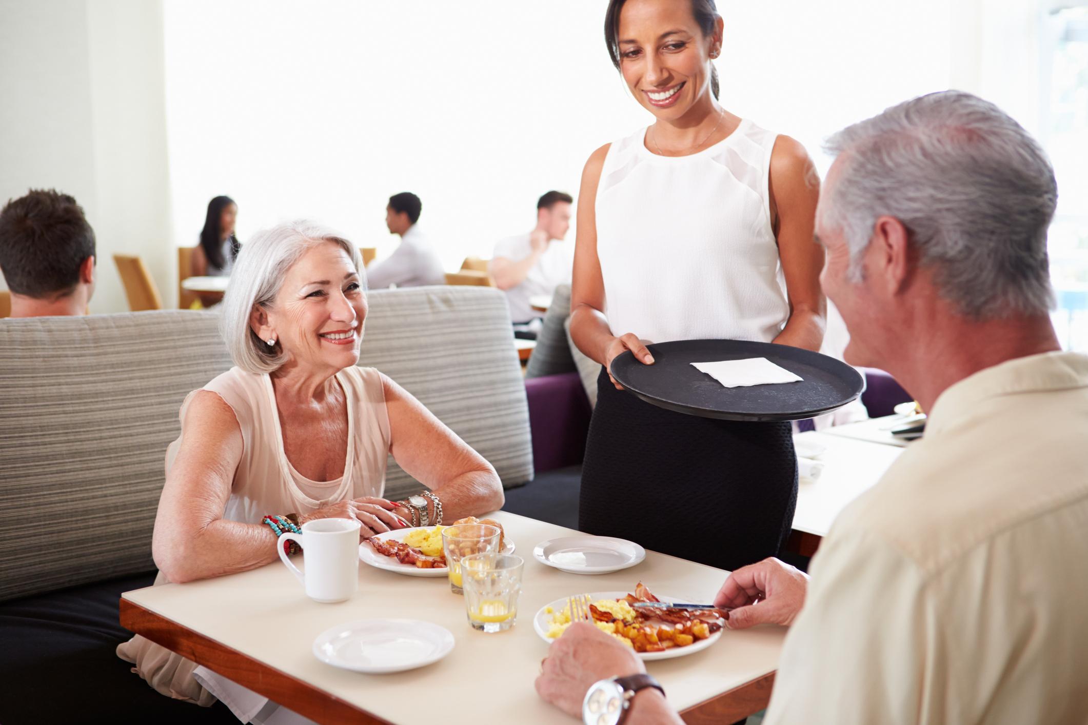 Waitress tending to seniors at a restaurant