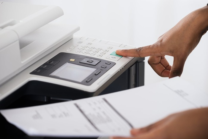 A person puts their finger on a copy machine.
