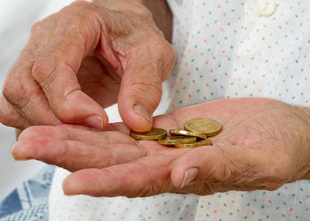 Coins in old woman's hands