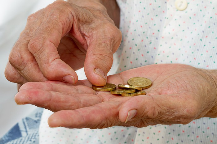 Close-up of an old woman's hands counting gold coins.