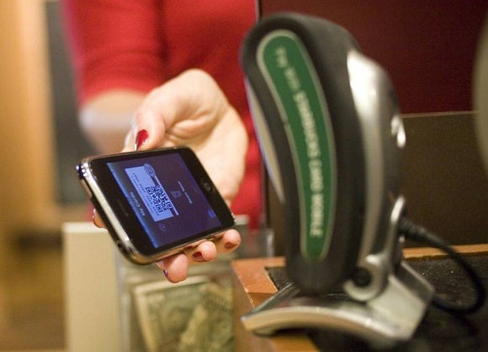 A woman uses her mobile device for payment at a Starbucks.